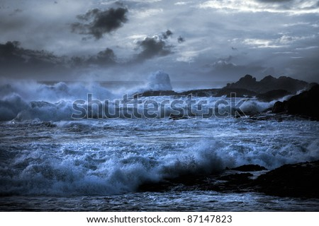 Storm in a beach in the Portuguese north coast with interesting waves; enhanced sky - stock photo