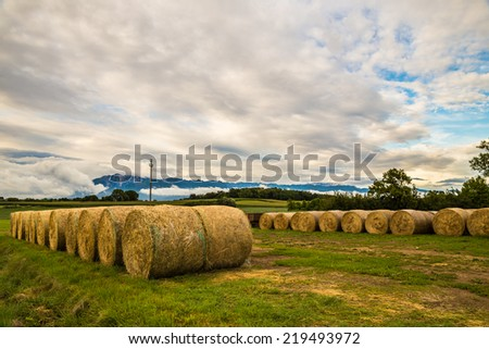storm is coming on a field with hay bales - stock photo