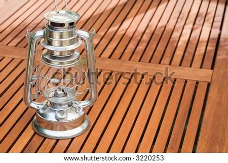 Storm lantern on wooden garden table. - stock photo