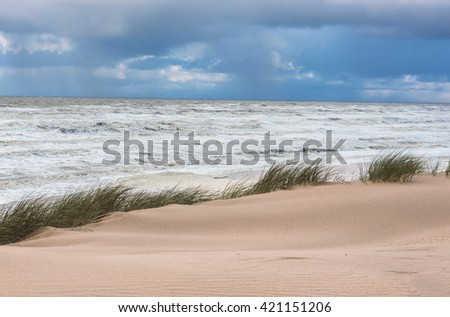 Storm over an ocean and sand dune - nature seascape background - stock photo