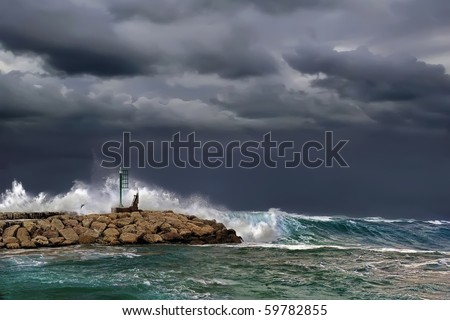 Storm, pier and small beacon - stock photo