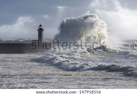 Storm waves over the Lighthouse, Portugal - blue sky - stock photo