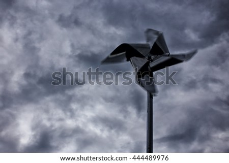 storm wind. metal toy pinwheel in rapid motion against the dark sky during a hurricane. non-flying weather.  blurred motion. copy space for your text - stock photo