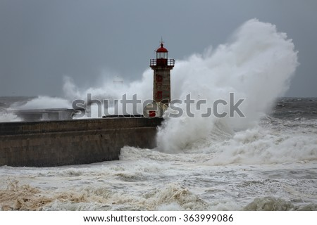 Stormy big wave over south piers and  lighthouses of river Douro harbor entry, north of Portugal - stock photo