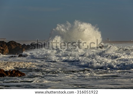 Stormy breaking wave in a sunny day. Beach from the north of Portugal. - stock photo