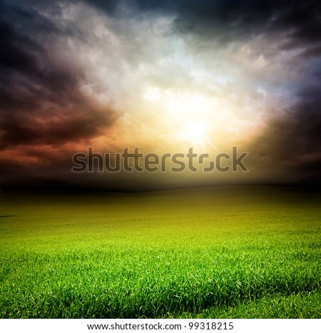 stormy dramatic sky and green field of grass with sun light passing through the clouds in the evening