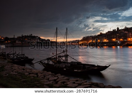Stormy evening sky above cities of Porto and Vila Nova de Gaia in Portugal, Rabelo boats on Douro river. - stock photo
