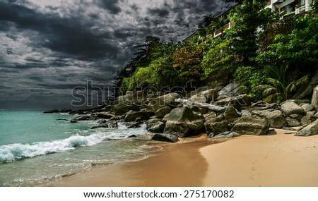 Stormy landscape with dark skyes on background and flash of sunlight on greenery, rocks and sand on foreground, house can be seen between leaves, footsteps on sand - stock photo