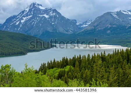 Stormy Lower Two Medicine Lake - A stormy spring evening view of Lower Two Medicine Lake and Rising Wolf Mountain at Two Medicine Valley region of Glacier National Park, Montana, USA. - stock photo