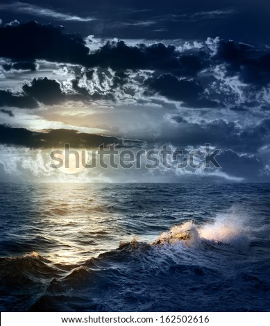 Stormy Sea at Night with dramatic sky and the big Moon -  beautiful and dangerous weather - stock photo
