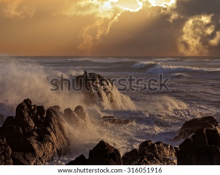 Stormy sea waves against coast cliffs at orange sunset (enhanced sky) - stock photo