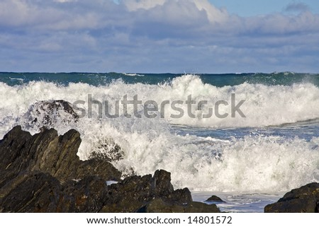 Stormy sea with waves braking on the rocks - stock photo