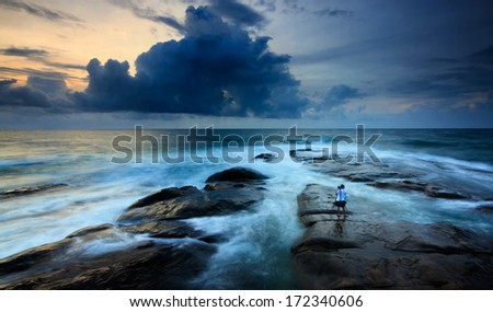 stormy seascape with lone photohrapher at the Tip of Borneo, Sabah, Malaysia - stock photo
