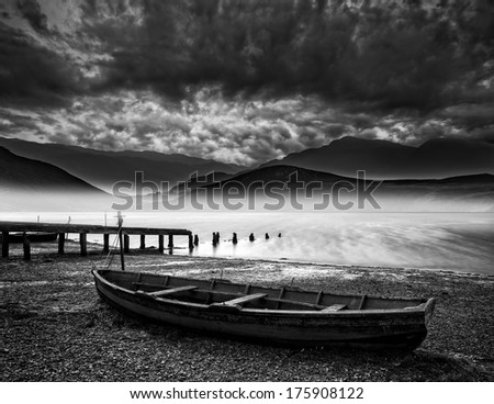 Stormy sky landscape over misty mountain lake with old boat on lake shore - stock photo