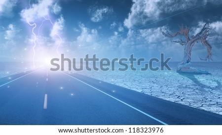 Stormy sky on desert road leading into city - stock photo