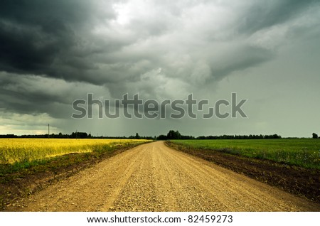 Stormy sky over the ground road. - stock photo