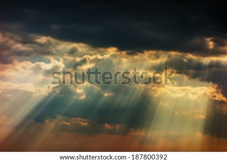 Stormy sky with a dramatic sunrays between the clouds on spring evening in Greece