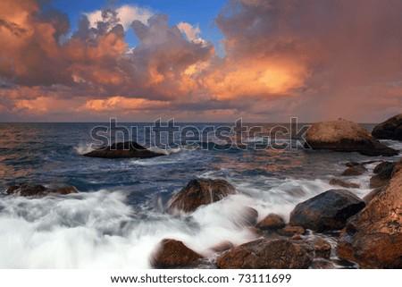 Stormy sunrise on the coast of tropical sea - stock photo