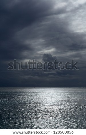 Stormy sunset over Aitutaki lagoon, Cook Islands, monochrome background.