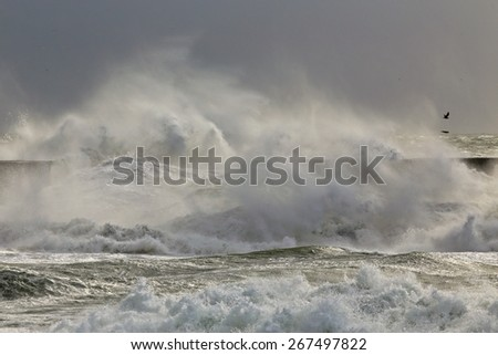 Stormy waves over a pier in the portuguese west coast - stock photo