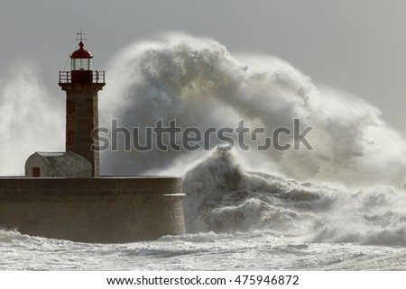 Stormy waves over lighthouse and pier with interesting autumn light. Douro river mouth, Porto, Portugal.
