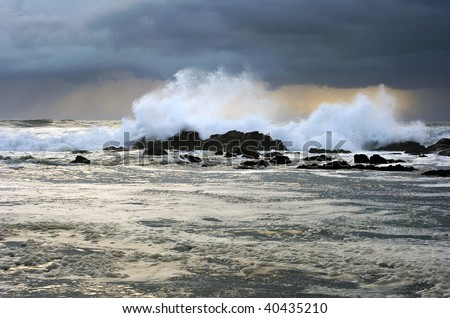 Stormy weather approaching the shore at sunset; Portugal - stock photo