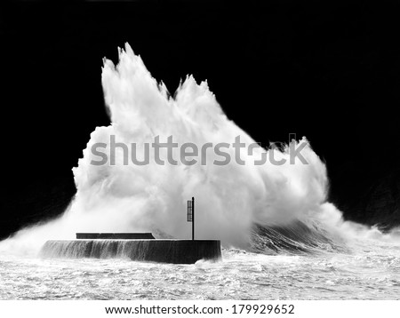 stormy weather on sea with big wave breaking on breakwater - stock photo