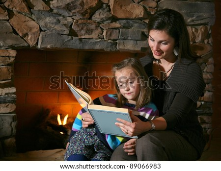 Story Time with Mother and Daughter in Front of Fireplace - stock photo