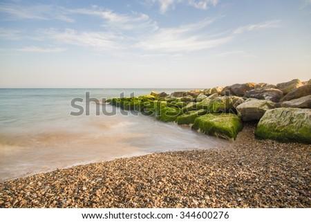 Stoune / boulder groyne on shingle / pebble beach on a summer day in the UK  - stock photo