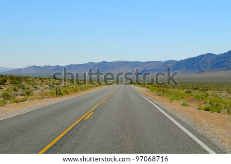 Straight and empty road with yellow lines. Nevada, US