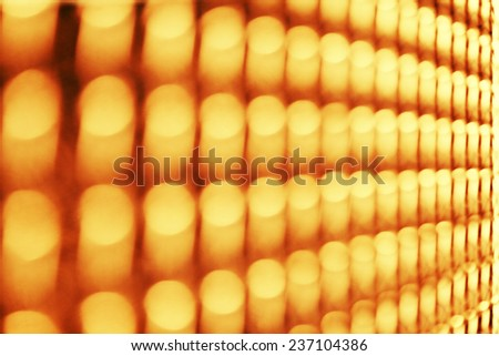 Straight and symmetric row of blurred yellow lights - stock photo