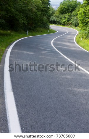 Straight asphalt road leading into the distance - stock photo