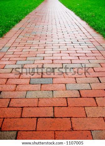Straight brick path cuts through bright green grass. - stock photo