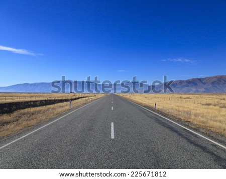Straight empty Country Road leading to Mountains lining the horizon on sunny day, Otago region, South Island, New Zealand. - stock photo