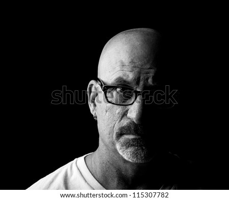 Straight on black and white head shot of a middle aged man looking into camera with facial hair and glasses with half his face shadowed on a black background