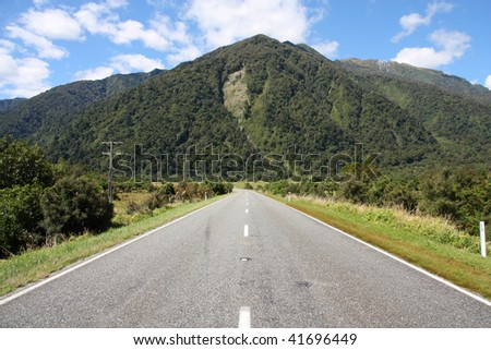 Straight road and mountains in green New Zealand. Temperate rainforest in West Coast region. - stock photo