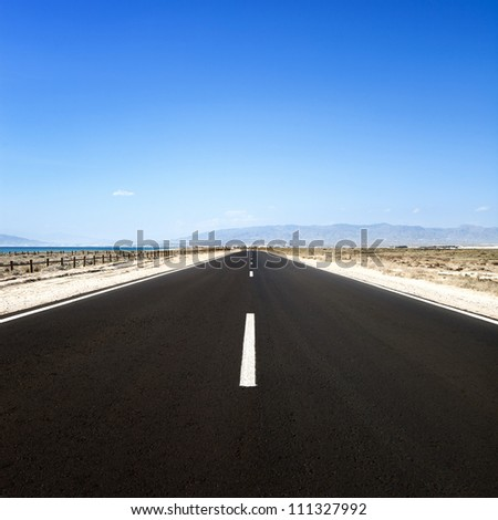 Straight road in a desert seascape in a sunny day. Cabo de Gata, Andalusia, Spain. - stock photo