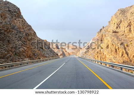 Straight road in the Sultanate of Oman - stock photo