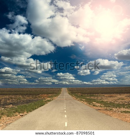 straight road near sea under sunny day and cloudy sky