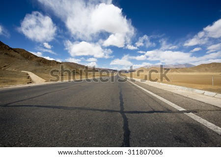 Straight road to the Himalayan mountain range on the Friendship Highway in Tibet. China - stock photo