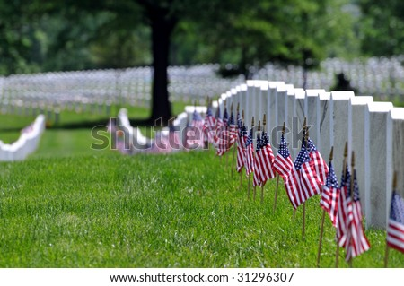 Straight row of graves at the Arlington National Cemetery in Arlington, Virginia, near Washington DC, on Memorial Day, with flags at each grave, narrow DOF