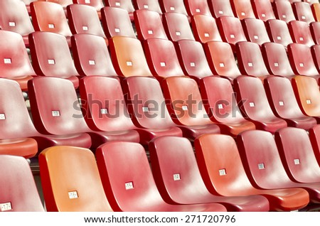 straight rows of red chairs in a sports stadium photographed at an angle - stock photo