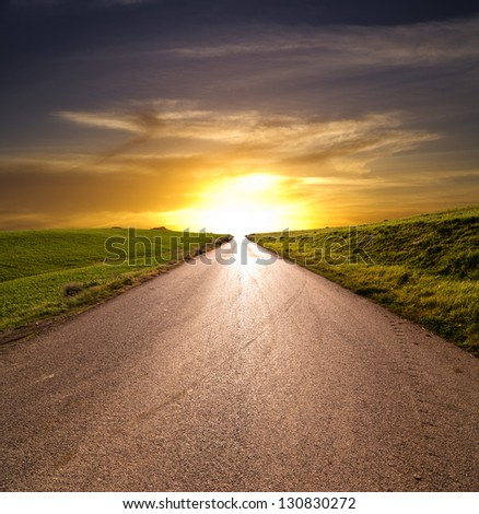 straight rural road at the sunset - stock photo
