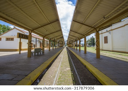 Straight train rail way in empty old outdoors train station in Salta, North of Argentina - stock photo
