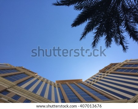 Straight up looking shot of a tall generic tropical resort style building with a palm tree. Airplane flies over as tourist travel on vacation. - stock photo