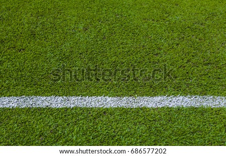 Straight white line on green empty football / soccer field grass.