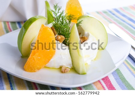 Strained yogurt labneh citrus salad with peeled oranges and green apples garnished with dill and walnuts served with oil - stock photo