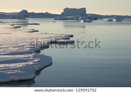 Strait between the Antarctic islands partially covered with ice. - stock photo
