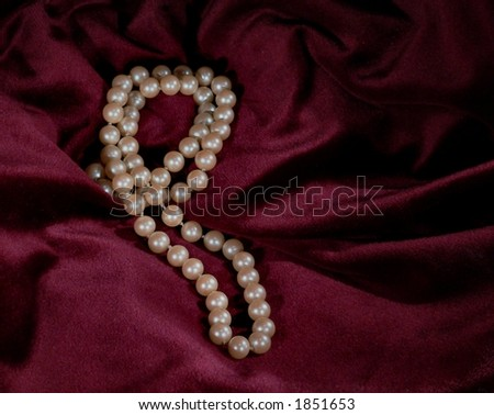Strand of pearls on luxurious burgundy fabric