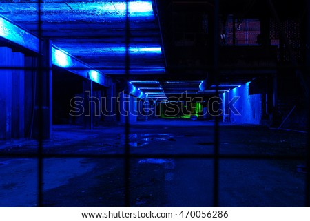 Strange and dark empty older warehouse / commercial space lit in blue at night